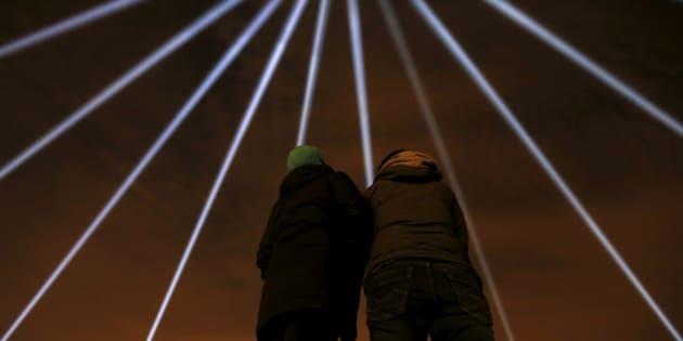 Des faisceaux lumineux éclairant le ciel de Montréal lors des commémorations de 2015.