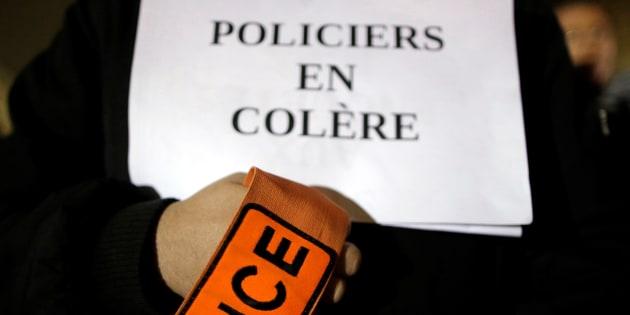 Un policier porte un écriteau lors d'une manifestation le 1er novembre à Paris.  REUTERS/Christian Hartmann