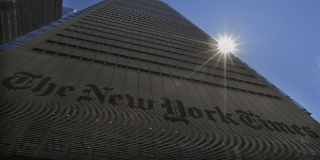 The sun peeks over the New York Times Building in New York Aug. 14, 2013.