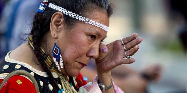 La survivante des pensionnats autochtones Patricia Tucknaow verse une larme lors d'un hommage aux survivants des pensionnats à Vancouver le 11 juin 2015.