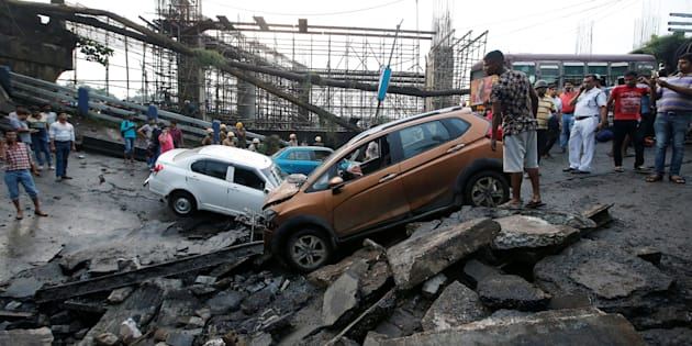 People stand next to the wreckage of vehicles at the site of a bridge that collapsed in Kolkata, India September 4, 2018. REUTERS/Rupak De Chowdhuri