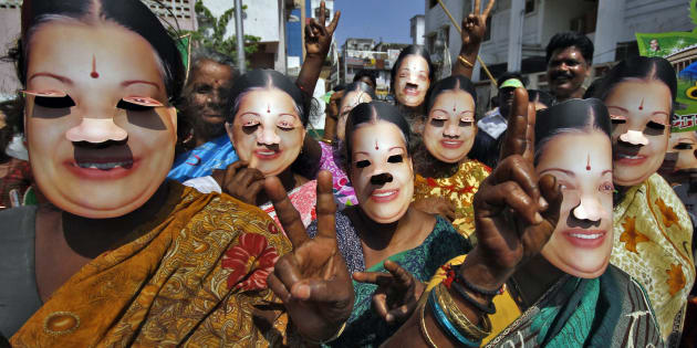 Supporters of J. Jayalalithaa wear masks as they gesture during an election campaign ahead of the general elections in Chennai, March 21, 2014.