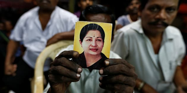 A supporter of Tamil Nadu Chief Minister J Jayalalithaa holds her photo. REUTERS/Danish Siddiqui