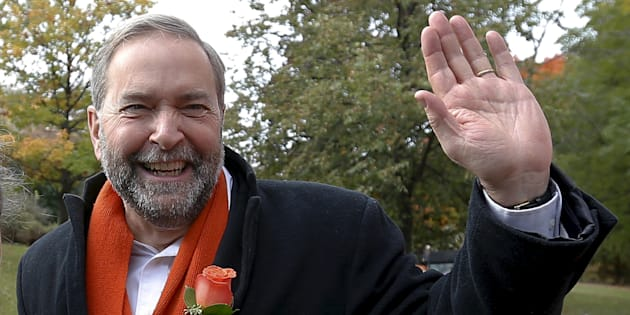 Tom Mulcair waves after visiting a zone house in Montreal, Quebec on Oct. 19, 2015.