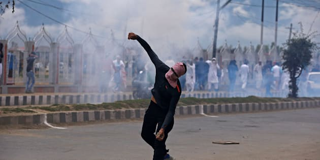 A demonstrator hurls a stone amid smoke from a tear gas shell fired by the Indian police during clashes after the Eid al-Adha prayers in Srinagar, September 2, 2017. REUTERS/Danish Ismail