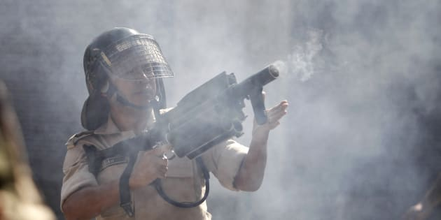 An Indian police officer fires tear gas towards protesters during a protest march in Srinagar.