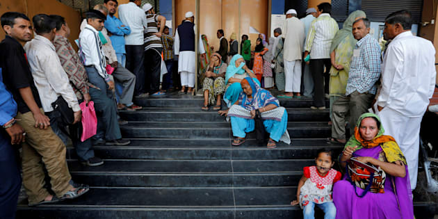 People wait for a bank to open to withdraw and deposit their money in Ahmedabad.