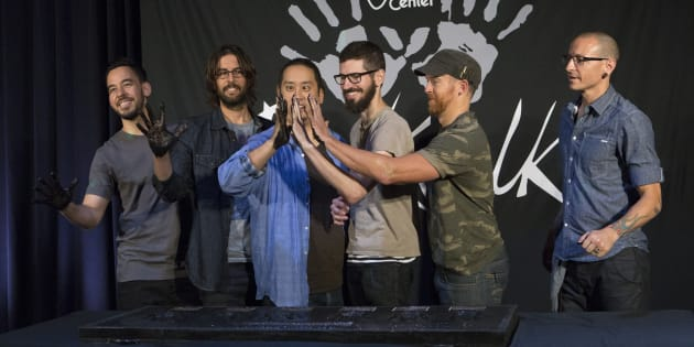 Members of rock band Linkin Park (from L-R) Mike Shinoda, Rob Bourdon, Joe Hahn, Brad Delson, Dave Farrell and Chester Bennington show their hands covered in cement as they are inducted into Guitar Center's RockWalk in Los Angeles, California June 18, 2014.    REUTERS/Mario Anzuoni  (UNITED STATES - Tags: ENTERTAINMENT)