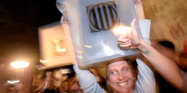 Una mujer sostiene feliz una de las urnas usadas en el referéndum del pasado 1 de octubre, en Barcelona.