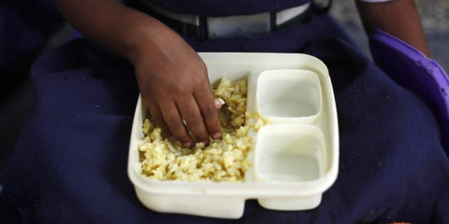 File photos of a schoolgirl eating her free mid-day meal, distributed by a government-run primary school, in New Delhi July 5, 2013.