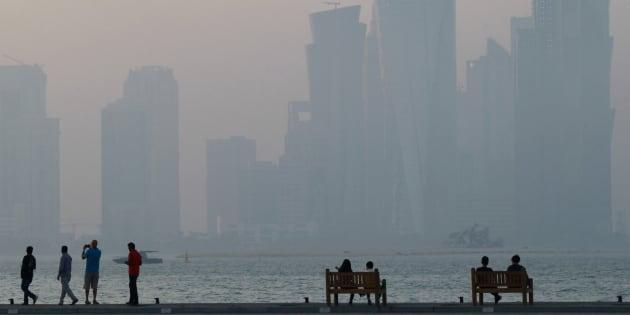 Un grupo de personas, descansando en la 'corniche' de Doha (Qatar).