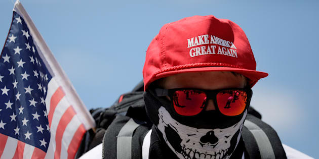 "A masked demonstrator in a Donald Trump ""Make America Great Again"" hat listens to speeches as self proclaimed ""White Nationalists"", white supremacists and ""Alt-Right"" activists gather for what they called a ""Freedom of Speech"" rally at the Lincoln Memorial in Washington, June 25, 2017."