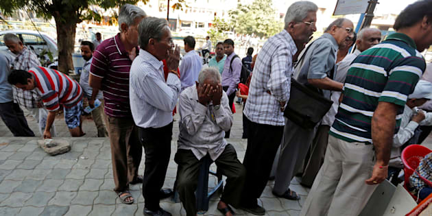 A man sits in a queue to deposit or exchange his old high denomination banknotes outside a bank in Ahmedabad, India November 21, 2016. REUTERS/Amit Dave
