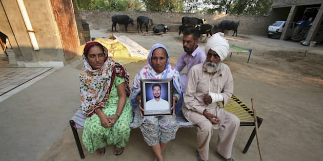 Malkit Kaur, mother of Kuldeep Singh, a cotton farmer who committed suicide, holds his portrait as Kuldeep's father Thana Singh (R), his brother Hardeep Singh (2nd R) and his widow Bhinder Kaur (L) sit on a cot at their residence on the outskirts of Bhatinda in Punjab, India, October 28, 2015.