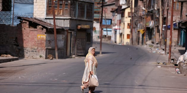 A woman crosses a deserted road during a curfew in Srinagar.