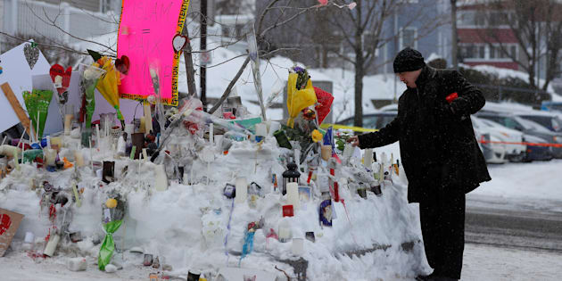 A man puts a candle at the memorial near the site of a fatal shooting at the Quebec Islamic Cultural Centre in Quebec City, Jan. 31, 2017.