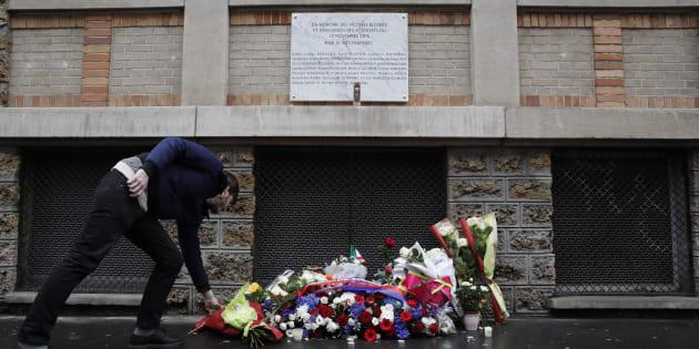 """Un homme déposant des fleurs sous la plaque commémorative installée près du café """"La Belle Equipe"""" le 13 novembre 2016."""
