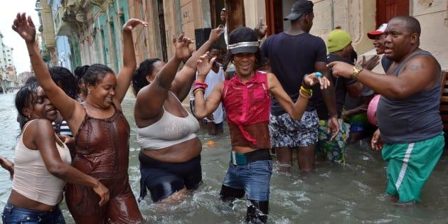 Vecinos de La Habana (Cuba) bailan en mitad de la calle anegada, tras el paso del Irma.