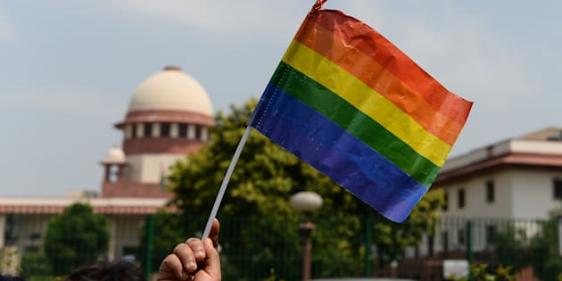 A member of the LGBT community waves a flag outside the Supreme Court building as crowds gathered to celebrate the decision to strike down the colonial-era ban on gay sex.