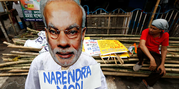 A supporter of Congress party sits next to an effigy of Indian Prime Minister Narendra Modi during a protest against the implementation of the Goods and Services Tax (GST) in Kolkata, July 2, 2017.