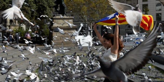 Una joven corre entre las palomas con una estelada al aire, esta mañana en Barcelona.