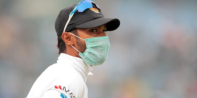 A Sri Lankan player, wearing a face mask, stands in the field. REUTERS/Stringer