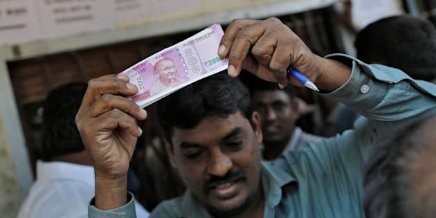 A man holds 2000 Indian rupees notes as he gets out of a bank in Mumbai, India, November 24, 2016. REUTERS/Danish Siddiqui