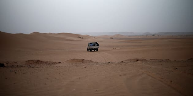 A vehicle transporting a group of African migrants drives through the desert on their journey from Ghat in southwest Libya May 29, 2014. A smuggler was transporting a group of African migrants through the desert to northern Libya. Libya's southwestern tip in the Sahara bordering Algeria and Niger has turned into an open door for illegal migrants from sub-Saharan countries heading for Europe, with the chaotic government in Tripoli appearing to have abandoned all control. The revolt that overthrew Libyan leader Muammar Gaddafi three years ago emptied Libya's arsenals, flooded the region with guns and dismantled much of the state apparatus, giving well-organised smuggler networks the run of the border. Border officials say up to 200 Africans cross the Ghat border strip every day, most headed north to the Mediterranean coast for the onward trip to Europe by boat. Picture taken May 29, 2014. REUTERS/Ahmed Jadallah  (LIBYA - Tags: SOCIETY POLITICS IMMIGRATION)  ATTENTION EDITORS: PICTURE 17 OF 31 FOR PACKAGE 'MIGRANT FLIGHT THROUGH LIBYA' TO FIND ALL IMAGES SEARCH 'JADALLAH GHAT'