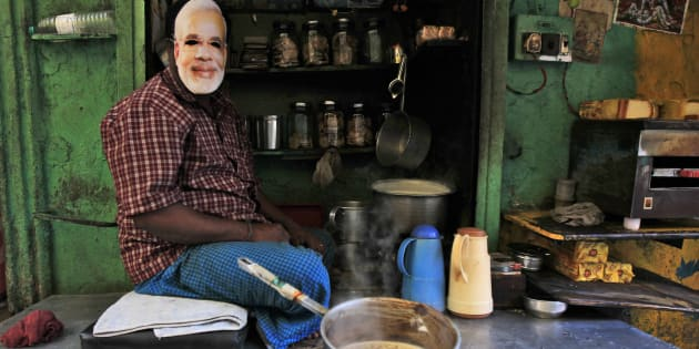 A tea stall vendor who is a supporter of India's main opposition Bharatiya Janata Party (BJP) poses while wearing a mask of Hindu nationalist Narendra Modi, prime ministerial candidate for BJP and Gujarat's chief minister, in Kolkata February 1, 2014. REUTERS/Rupak De Chowdhuri (INDIA - Tags: POLITICS ELECTIONS)