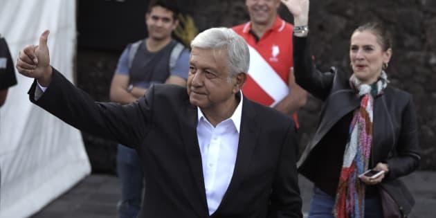 El candidato presidencial Andrés Manuel López Obrador es seguido por su esposa esposa Beatriz Gutiérrez Muller (R) mientras muestra su pulgar manchado de tinta después de votar en una mesa electoral durante las elecciones presidenciales en la Ciudad de México.