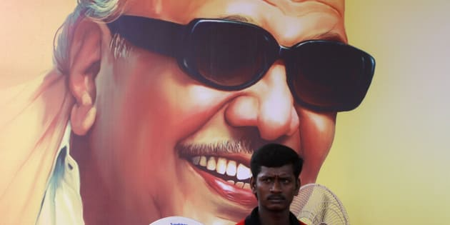 A supporter of Dravida Munnetra Kazhagam (DMK) party sits in front of the poster of party chief M. Karunanidhi during a rally ahead of a general election, in the southern Indian city of Chennai March 26, 2014. India, the world's largest democracy, will hold its general election in nine stages staggered between April 7 and May 12. REUTERS/Babu (INDIA - Tags: POLITICS ELECTIONS)