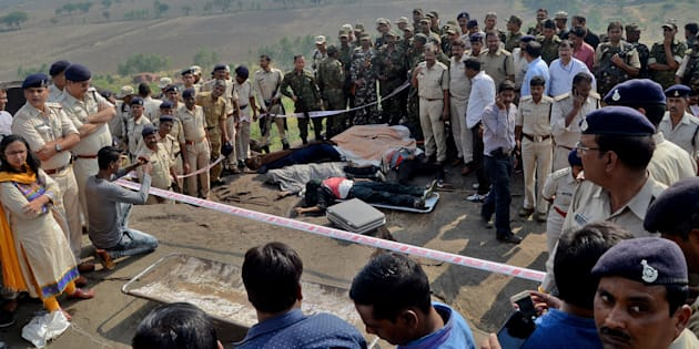 Police officers and Special Task Force soldiers stand beside dead bodies of the suspected members of the banned Students Islamic Movement of India (SIMI), who escaped the high security jail in Bhopal, and later got killed in an encounter on the outskirts of Bhopal on 31 October 2016.
