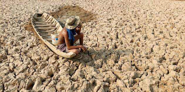 A fisherman sits on his boat in a dried-up pond in drought-stricken Cambodia in May 2016. Climate change has been linked to an increasein extreme weather events, including drought, hurricanes and wildfires, worldwide.