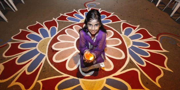 Shanaya Persad holds a diya, or oil lamp, in a street during Diwali celebrations in Felicity, central Trinidad.