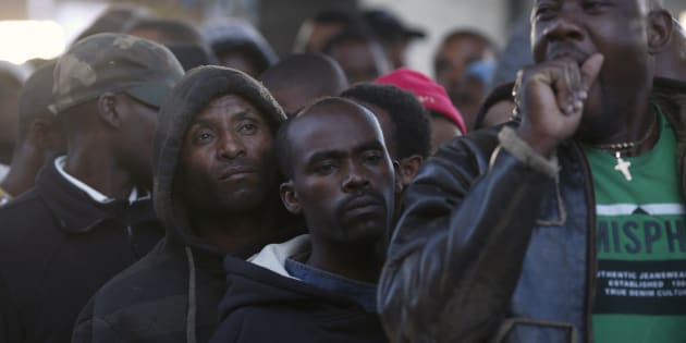 Asylum seekers queue to get their documents renewed outside a Department of Home Affairs reception centre in Cape Town on May 29, 2013.