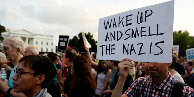 """People gather for a vigil in response to the death of a counter-demonstrator at the """"Unite the Right"""" rally in Charlottesville, outside the White House in Washington, U.S. August 13, 2017."""