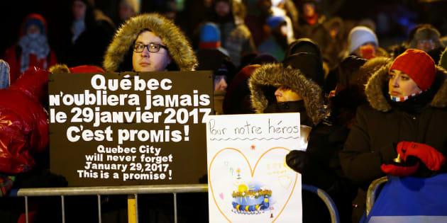 Les gens tiennent des pancartes de soutien lors d'une vigile soulignant la première Commémoration des victimes de la fusillade mortelle survenue au Centre Culturel Islamique de Québec à Québec, en janvier 2018.