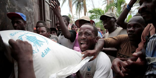 Haitians fight over a sack of rice distributed by humanitarian aid workers after Hurricane Matthew ripped through the tiny nation.