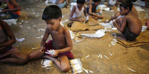 Des enfants remplissent des cigarettes vides manuellement avec du tabac cultivé localement, dans une petite usine à Haragach, Bangladesh, en juillet 2013.