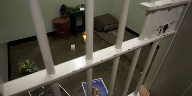 A lit candle in former South African president Nelson Mandela's cell on Robben Island, as part of a night vigil in December 2013 to honour Mandela.