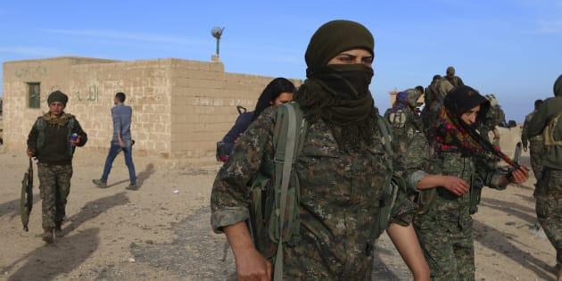 Des combattants des Forces démocratiques syriennes transportent leurs armes dans le village de Ghazila après avoir pris le contrôle de la ville des forces de l'État islamique, en février 2016.
