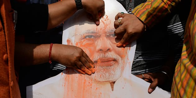A placard with the image of India's Prime Minister Narendra Modi is covered with colored powder by Indian supporters of the Bharatiya Janata Party (BJP) as they celebrate in the Indian capital New Delhi on March 3, 2018.