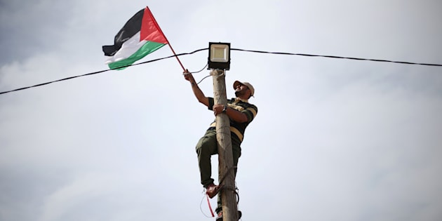 A man hangs a Palestinian flag from an electricity pole near the border with Israel in southern Gaza.
