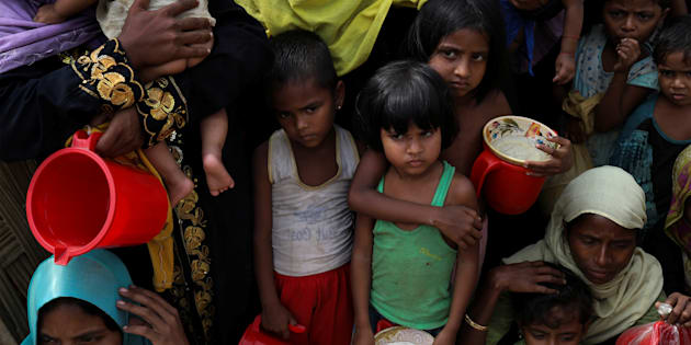 Rohingya women and children wait to get distributed meals at Moynarghona refugee settlement near Cox's Bazar, Bangladesh.