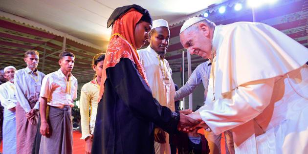 El papa Francisco se inclina ante una refugiada rohingya durante el acto interreligioso de hoy en la catedral de Dhaka, Bangladesh.