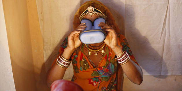 A villager goes through the process of eye scanning for Unique Identification (UID) database system at an enrolment centre at Merta district in the desert Indian state of Rajasthan February 21, 2013.In a more ambitious version of programmes that have slashed poverty in Brazil and Mexico, the Indian government has begun to use the UID database, known as Aadhaar, to make direct cash transfers to the poor, in an attempt to cut out frauds who siphon billions of dollars from welfare schemes. Picture taken February 21, 2013. REUTERS/Mansi Thapliyal (INDIA - Tags: BUSINESS SOCIETY POVERTY SCIENCE TECHNOLOGY)