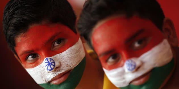 インドの国旗を顔にペイントし、独立記念日を祝うインド人の子ども。インドでは、子どもたちに高学歴を望む家庭が急速に増えている=2014年8月、インド北部のジャンムー