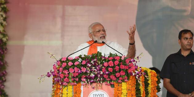 Indian Prime Minister Narendra Modi (L) addresses a gathering of Bhartiya Janta Party (BJP) supporters during Gujarat Gaurav Mahasamellan at Bhaat village on the outskirts of Ahmedabad on October 16, 2017.