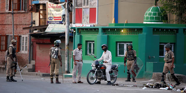 An Indian police officer stops a motorcyclist during a curfew in Srinagar July 13, 2016. REUTERS/Danish Ismail