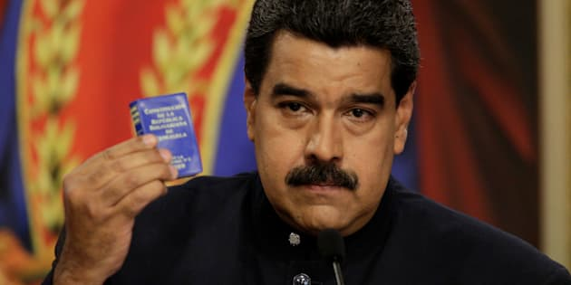 Venezuela's President Nicolas Maduro holds up a book of the country's constitution during a news conference at Miraflores Palace in Caracas, Venezuela August 22, 2017. REUTERS/Marco Bello